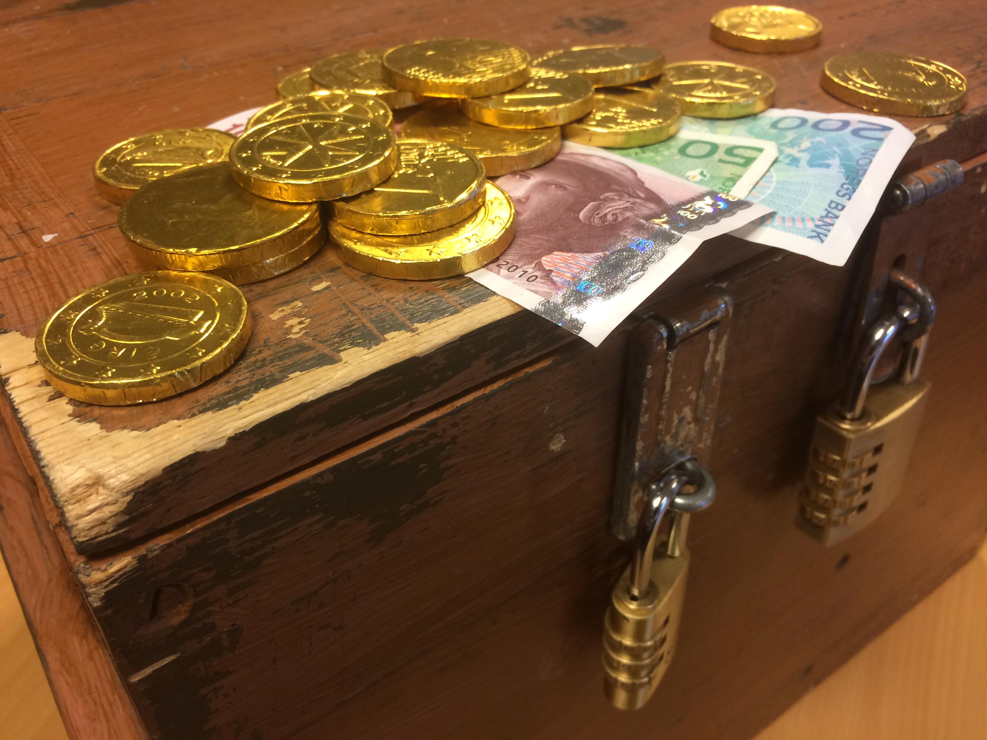 Kiste med hengelås og penger ligger på lokket