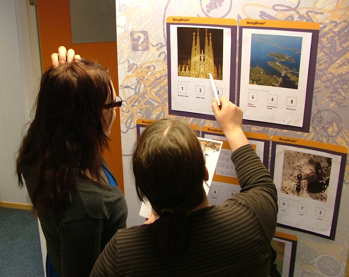 2 eventdeltagere løser oppgaver ved en RollUp-vegg