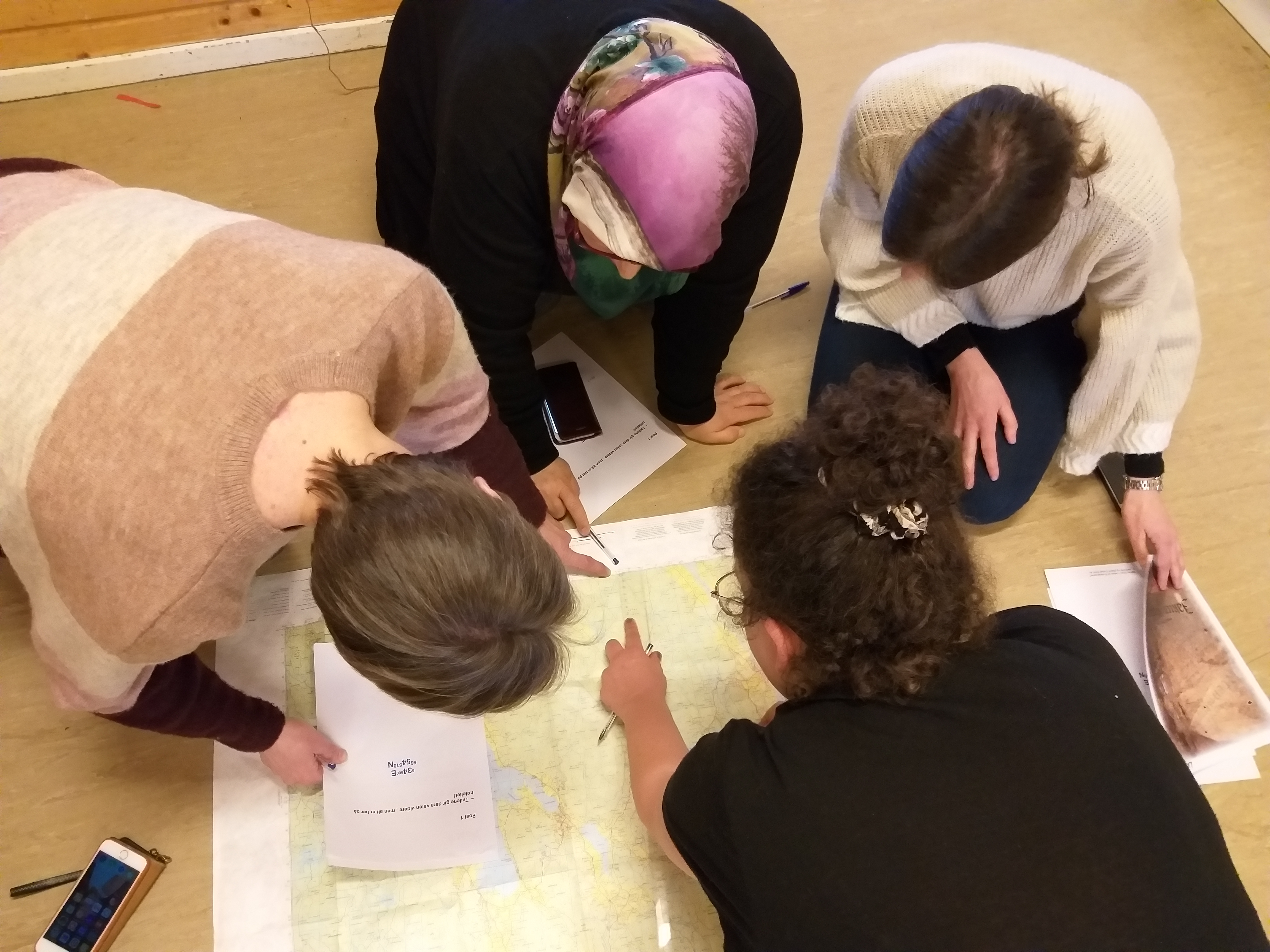 4 personer ligger på gulvet og løser kartoppgave