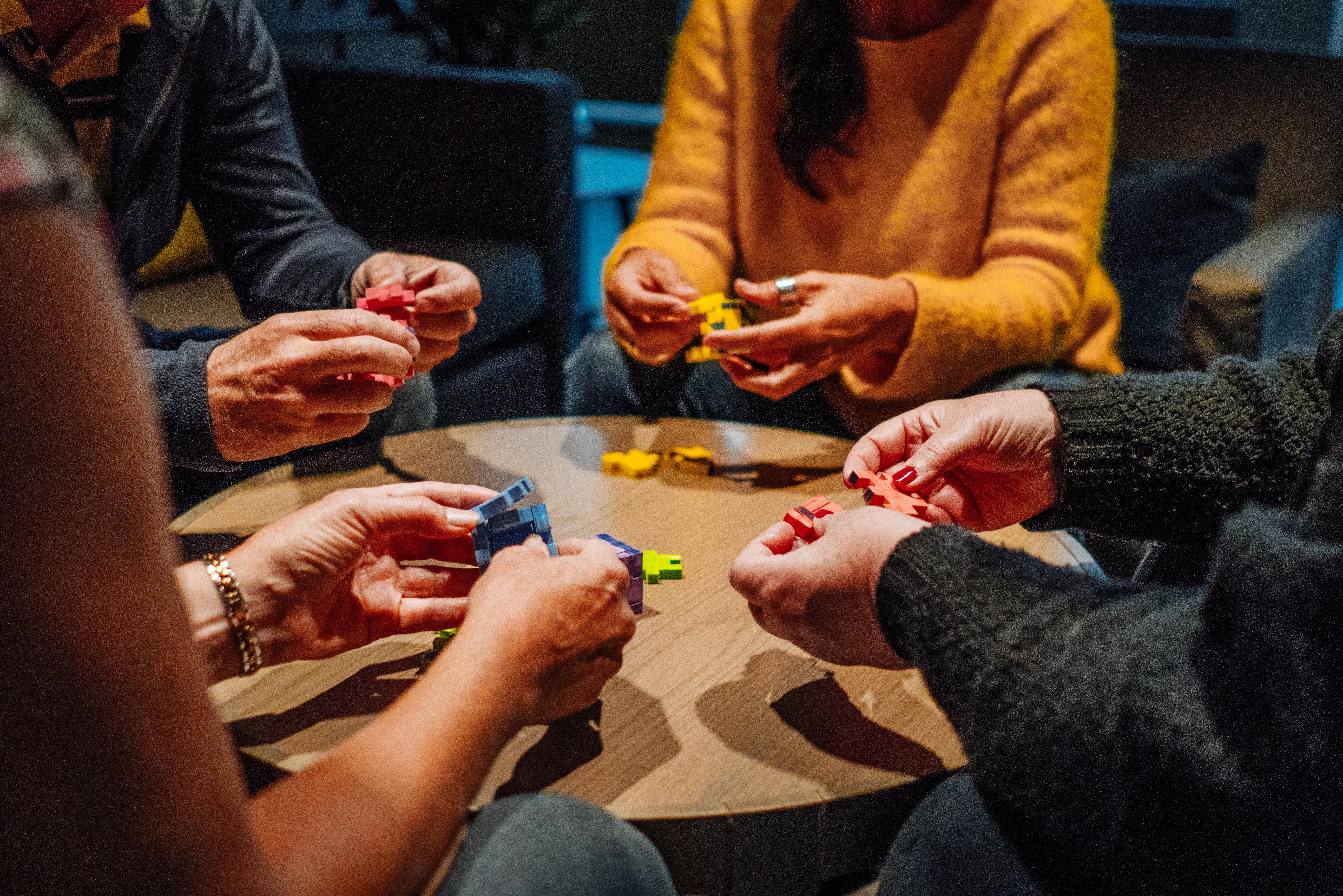 4 mennesker løser pusleoppgaver rundt et bord