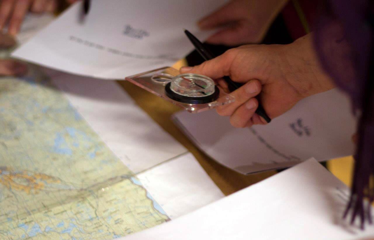 løseløser oppgave på bordet med kart og kompass
