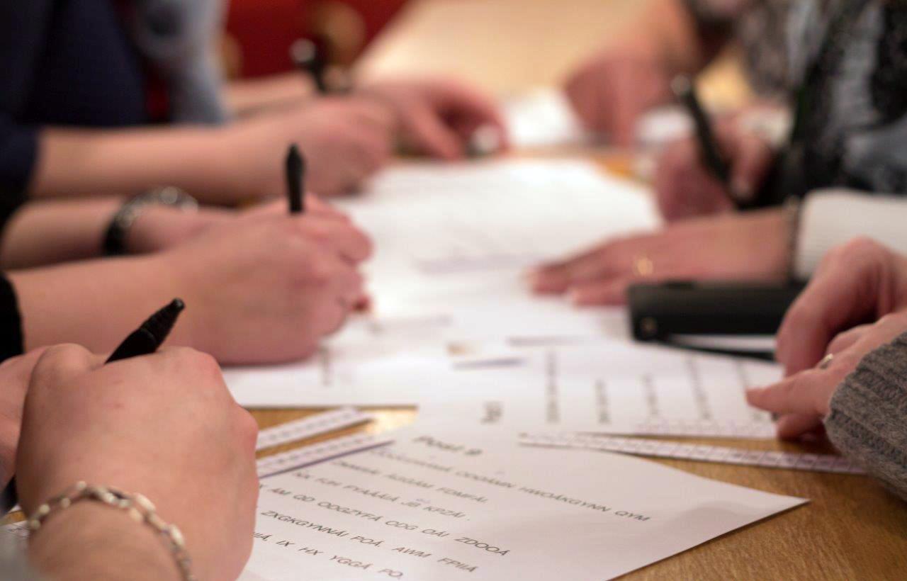 Mange hender rundt et bord løser oppgaver