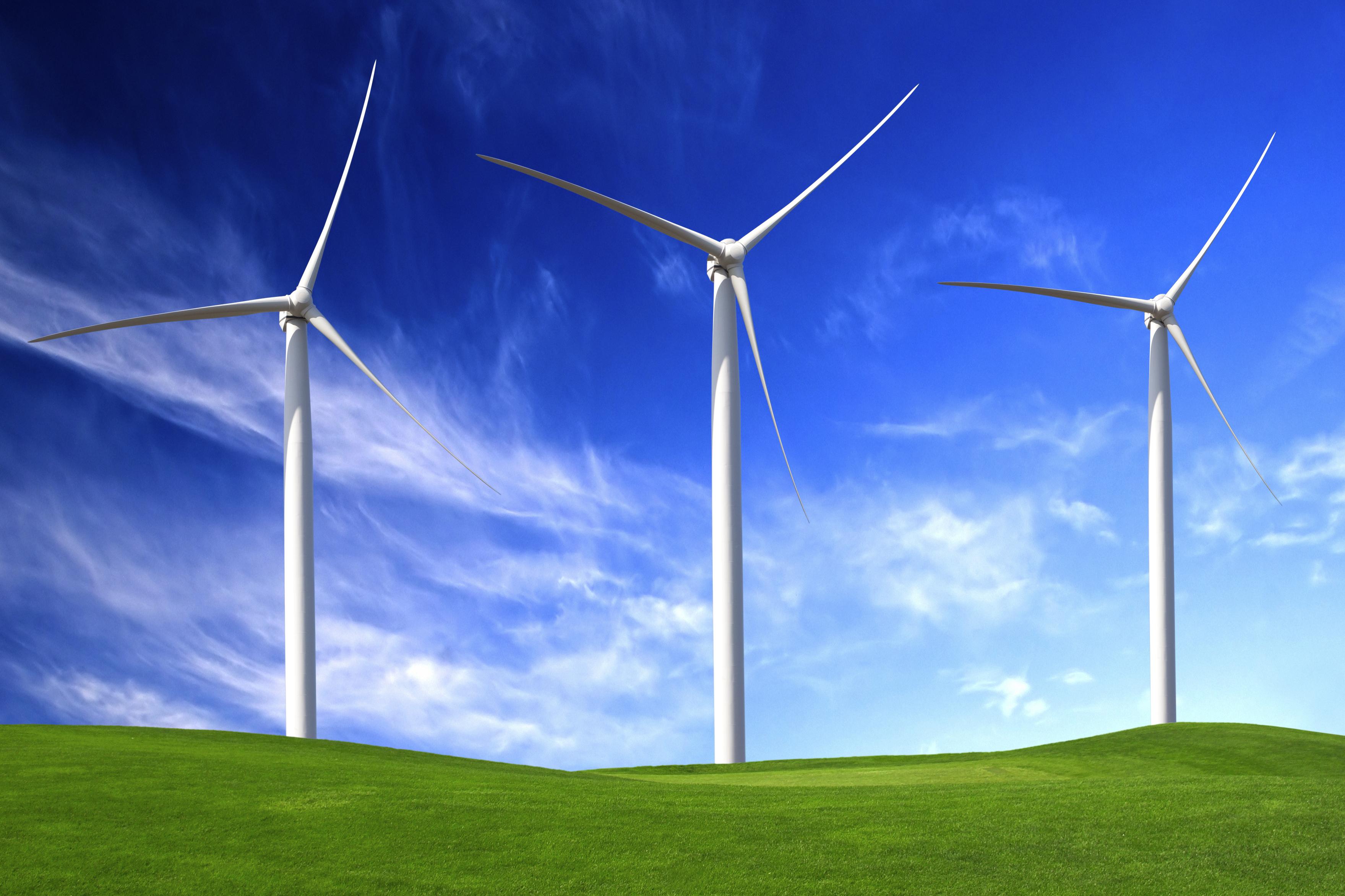 3 vindmøller i grønt landskap og blå himmel