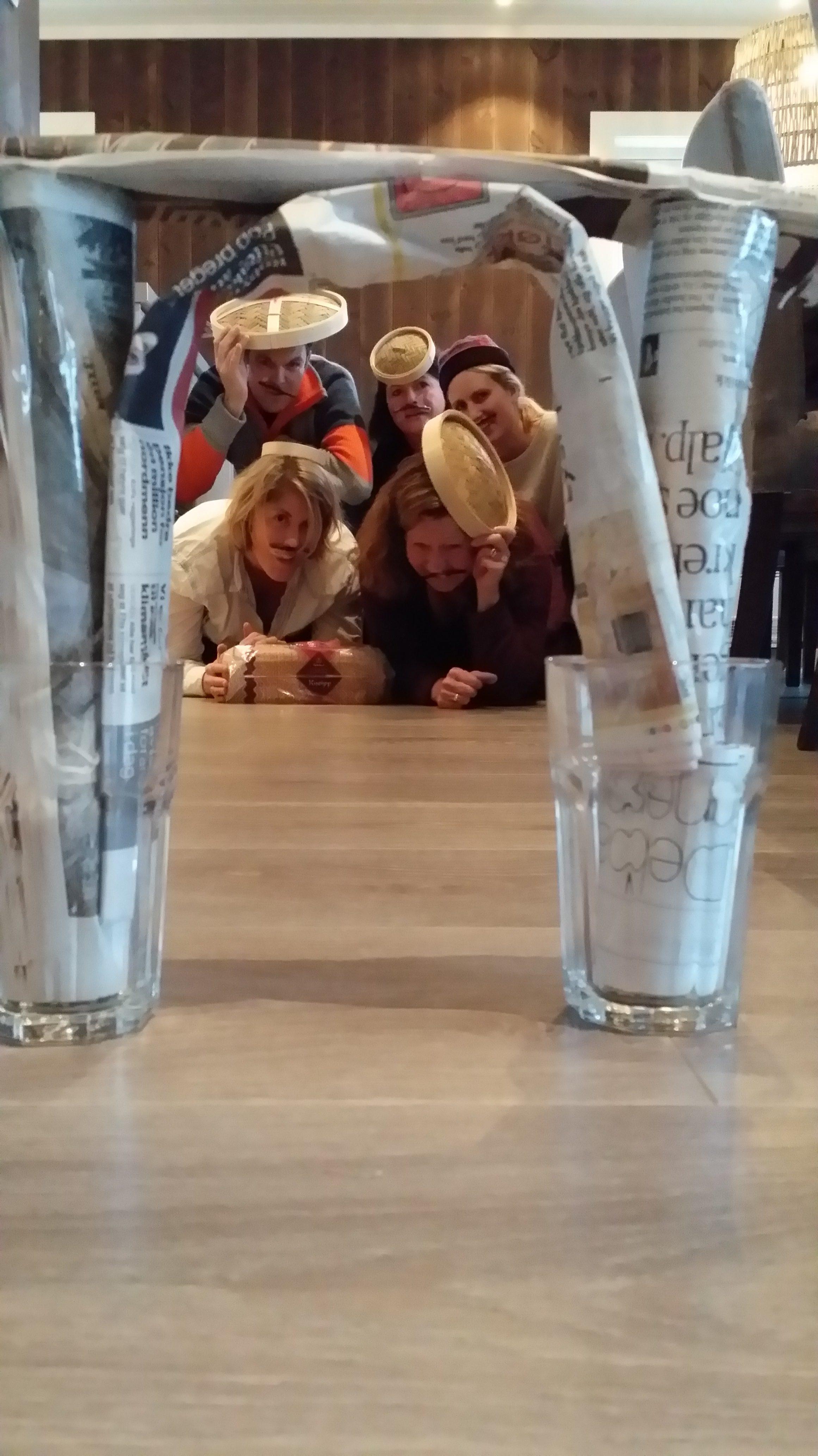 Gruppe mennesker ligger på gulvet bak en portal av avispapir