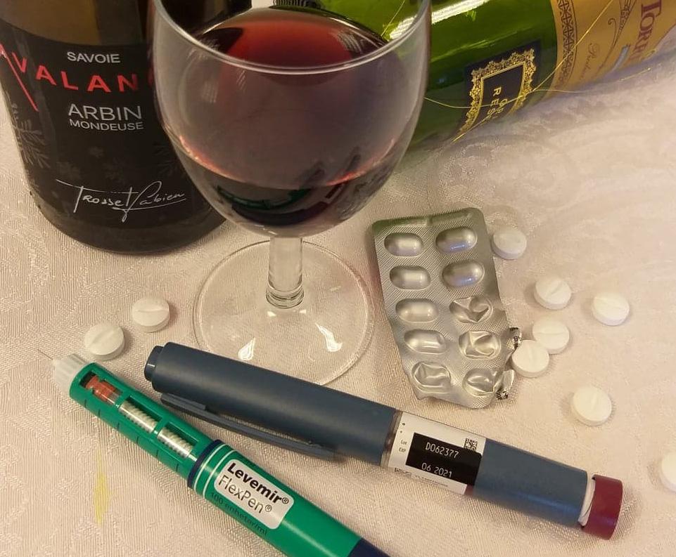 Piller insulin og vin på hvit duk